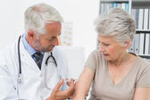 Male doctor injecting senior female patient — Stock Photo
