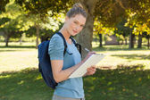 Beautiful young woman writing on clipboard at park — Stock Photo
