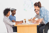 Group of artists in discussion at desk at office — Stock Photo
