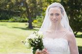 Bride smiling through veil in garden — Stock Photo