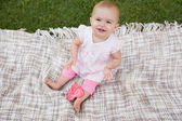 Cute baby with heart shaped lollipop sitting on blanket at park — Stock Photo