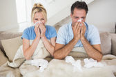 Couple suffering from cold in bed — Stock Photo