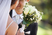Mid section of a newlywed couple with bouquet in park — ストック写真