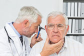 Close-up of a male doctor examining senior patient's ear — Stock Photo