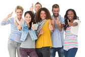 Happy group of young friends giving thumbs up to camera — Stock Photo