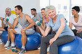 Fitness class with dumbbells sitting on exercise balls in gym — Stock Photo
