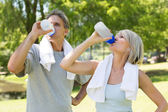 Couple drinking water after workout — Stock Photo