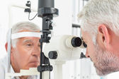 Optometrist doing sight testing for senior patient — Stock Photo