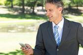 Businessman text messaging through cellphone — Stock Photo