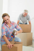 Happy couple sealing cardboard moving boxes — Stock Photo