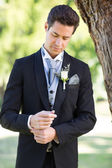 Groom adjusting sleeve at garden — Stock Photo