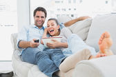 Couple watching funny movie lying on the sofa with bowl of popcorn — Foto de Stock