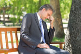 Depressed businessman in park — Stock Photo
