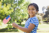 Girl holding the American flag at park — Stock Photo