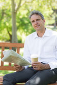 Businessman with cup and newspaper in park — Stock Photo