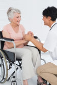 Doctor talking to a senior patient in wheelchair — Stock Photo