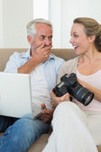 Happy couple viewing their photos on the laptop — Stock Photo