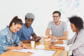 Group of happy artists in discussion at desk — Stock Photo