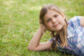 Girl lying on grass at park — Stock Photo