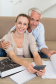 Smiling couple calculating their bills at the couch — Stock Photo