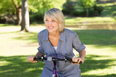 Woman riding bicycle in parkland — Stock Photo