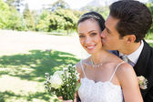 Groom kissing bride on cheek in garden — Stock Photo