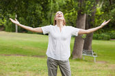 Woman with arms outstretched at park — Stok fotoğraf