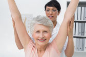 Female physiotherapist with senior woman raising hands — Stock Photo