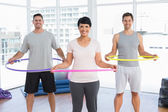 Fitness class holding hula hoops around waist in gym — Stock Photo