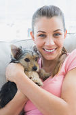 Smiling woman cuddling her yorkshire terrier on the couch — Stock Photo
