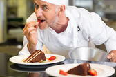 Smiling male pastry chef eating strawberry by dessert — Stock Photo