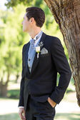 Bridegroom looking away in garden — Stock Photo