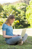 Relaxed young woman using laptop at park — Foto Stock