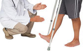 Doctor with senior man using walker — Stock Photo