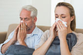 Sick couple blowing their noses sitting on the couch — Stock Photo