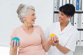 Doctor with senior patient using stress buster balls — Stock Photo