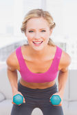 Fit blonde lifting dumbbells — Stock Photo