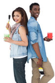 Couple with paintbrushes and containers — Stock Photo