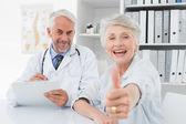 Felizes sênior pacientes gestos polegares para cima com o médico — Fotografia Stock