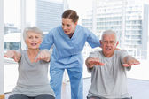 Female therapist assisting senior couple with exercises — Stock Photo