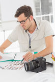 Concentrate male artist sitting at desk with photos — Stock Photo