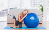 Blonde sitting beside exercise ball — Stock Photo