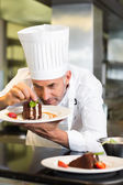 Concentrated male pastry chef decorating dessert in kitchen — Stock Photo