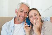 Happy couple listening to phone call together on the couch — Stock Photo