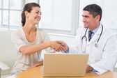 Doctor and patient shaking hands by laptop in office — Stock Photo