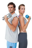 Portrait of a fit couple exercising with dumbbell — Stockfoto