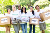 Volunteers carrying donation boxes in park — Stock Photo