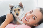 Happy woman cuddling her yorkshire terrier on the couch — Stock Photo