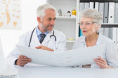 Doctor with patient reading reports at medical office — Stock Photo