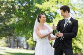 Newlywed couple opening champagne bottle — 图库照片